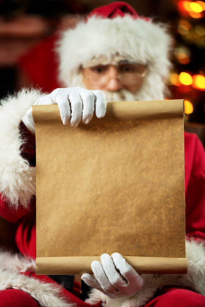 santa claus sitting at home and reading a list stock photo