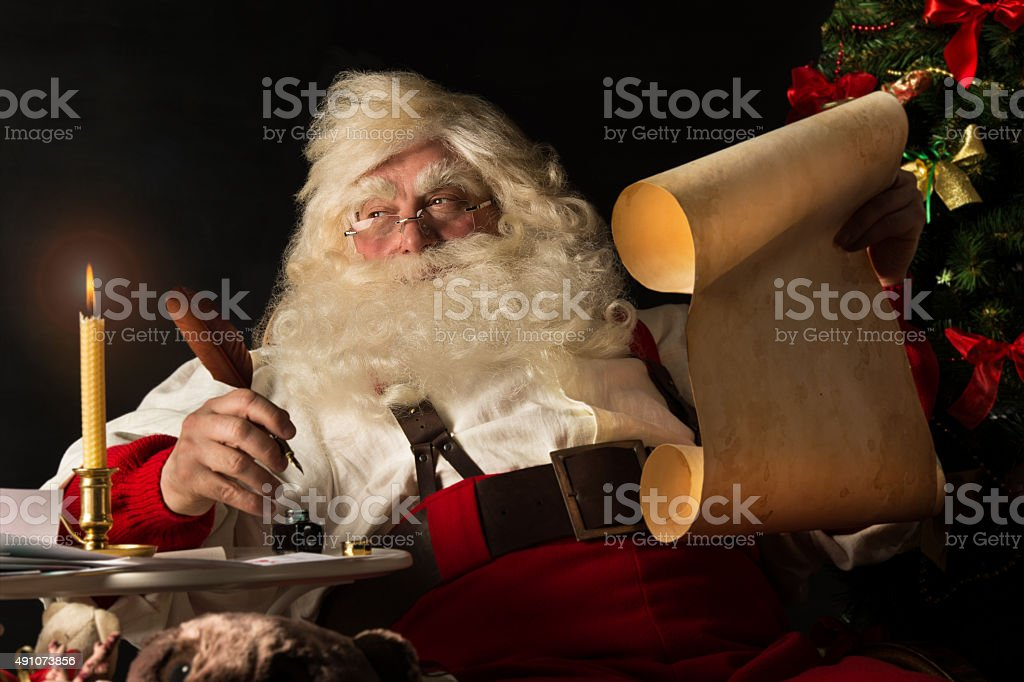 Santa Claus sitting at home and writing a letter stock photo