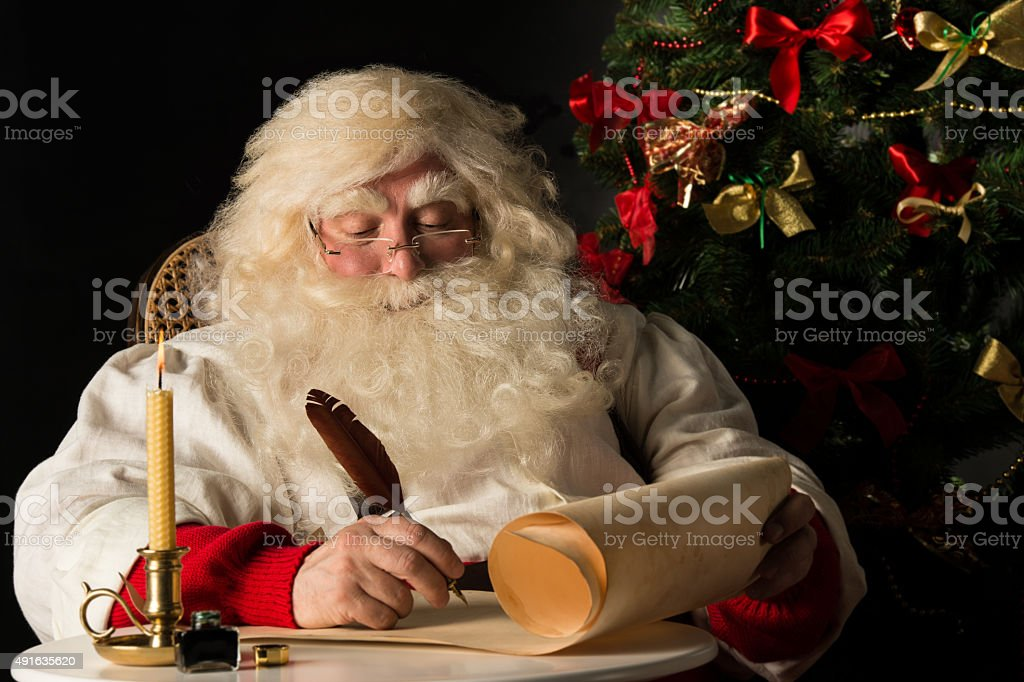 Santa Claus sitting at home and writing on paper roll stock photo