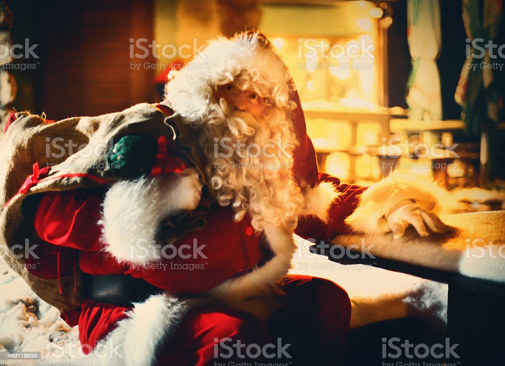 Santa Claus sitting in front of a house. stock photo