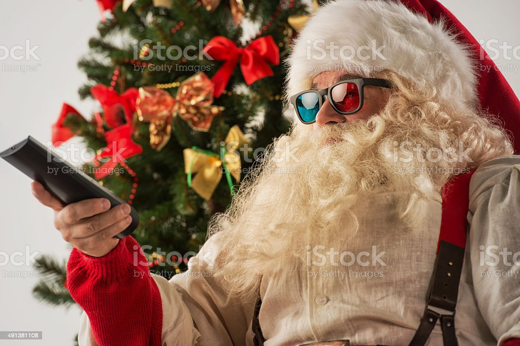 Santa Claus sitting in rocking chair near Christmas Tree stock photo