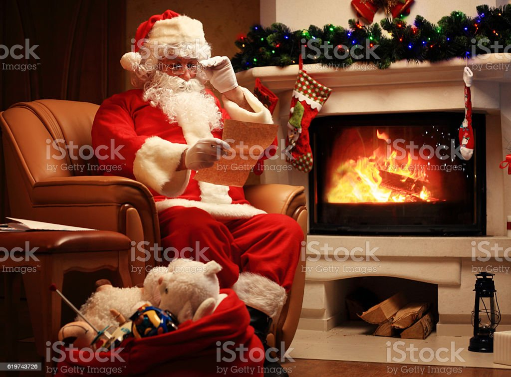 Santa Claus sitting near Christmas tree  and reading Christmas letter stock photo