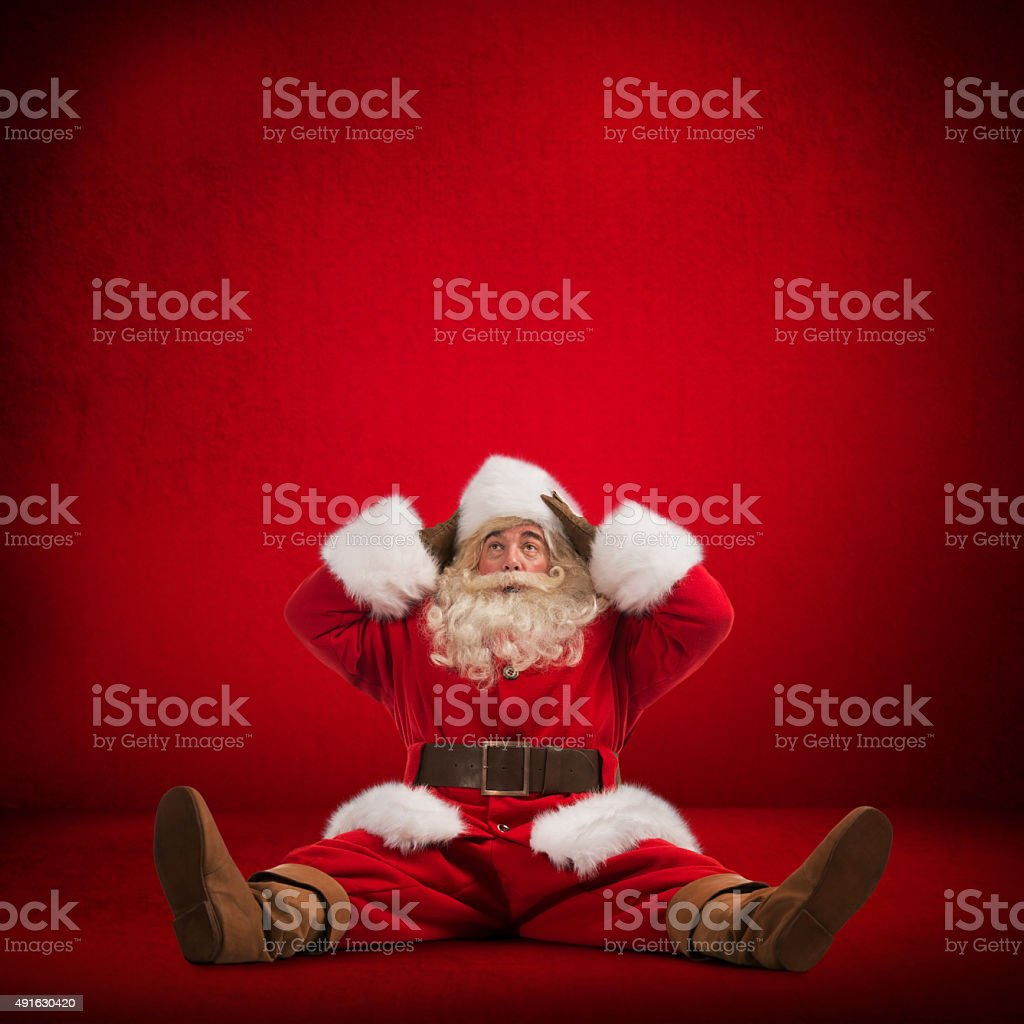 Santa Claus sitting on floor and looks frustrated stock photo