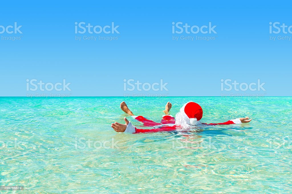 Santa Claus swimming in ocean water, Christmas concept stock photo