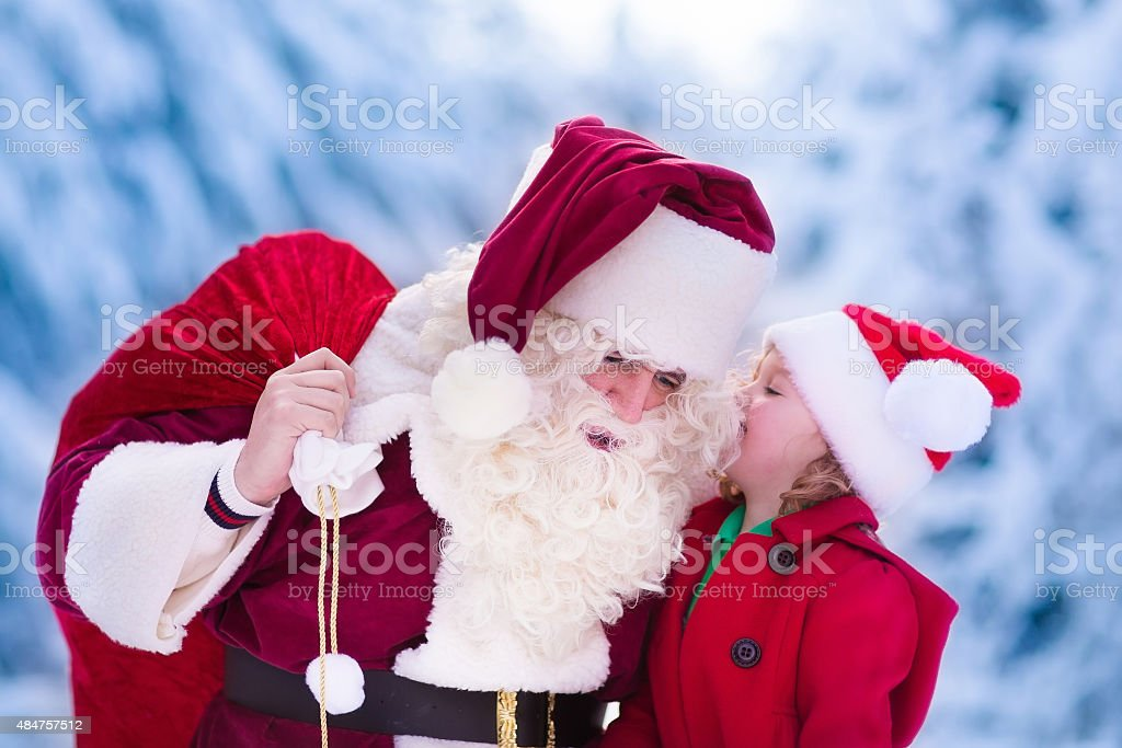 Santa Claus talking to little girl in snowy park stock photo