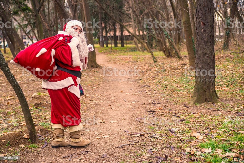 Santa Claus walking with the bag of the presents stock photo