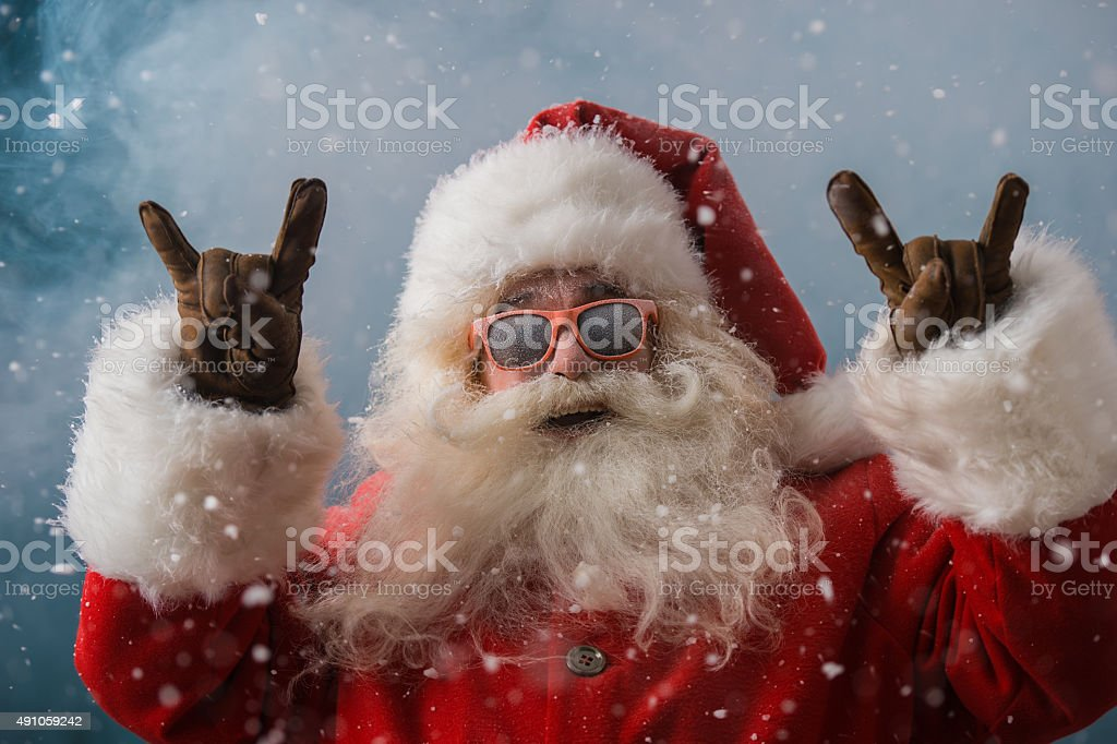 Santa Claus wearing sunglasses dancing outdoors at North Pole stock photo