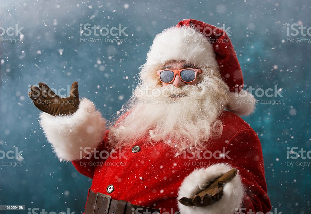 Santa Claus wearing sunglasses dancing outdoors at North Pole stock photo