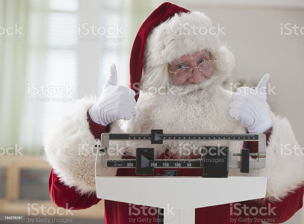 Santa Claus weighing himself with thumbs up stock photo
