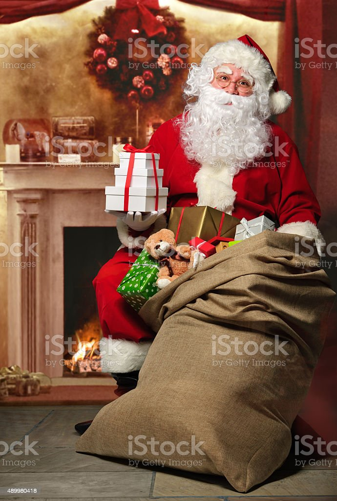 Santa Claus with a bag of presents at the fireplace stock photo