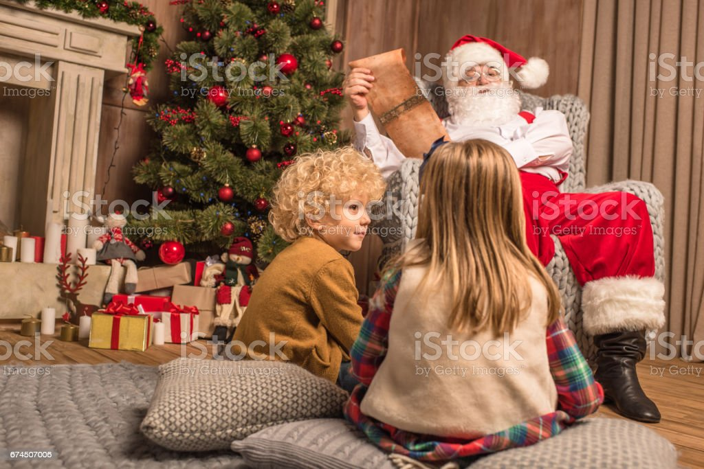 Santa Claus with children reading wishlist stock photo