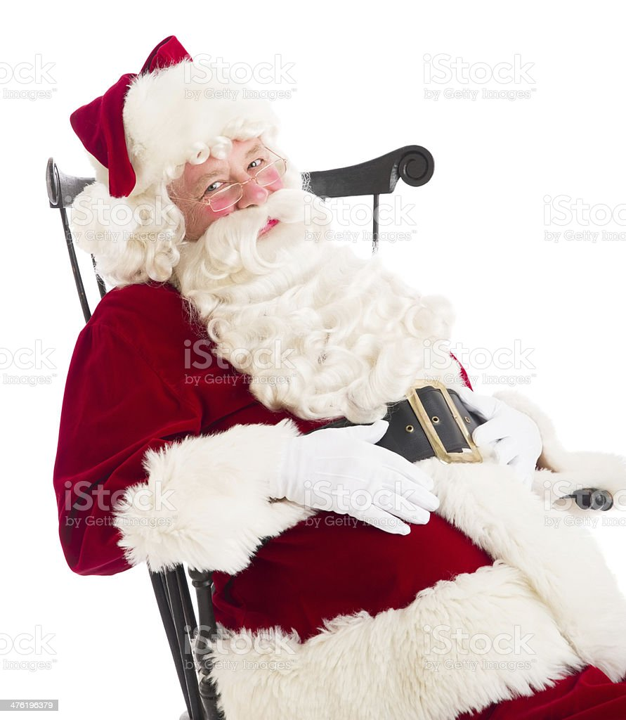 Santa Claus With Hands On Stomach Sitting In Chair royalty-free stock photo