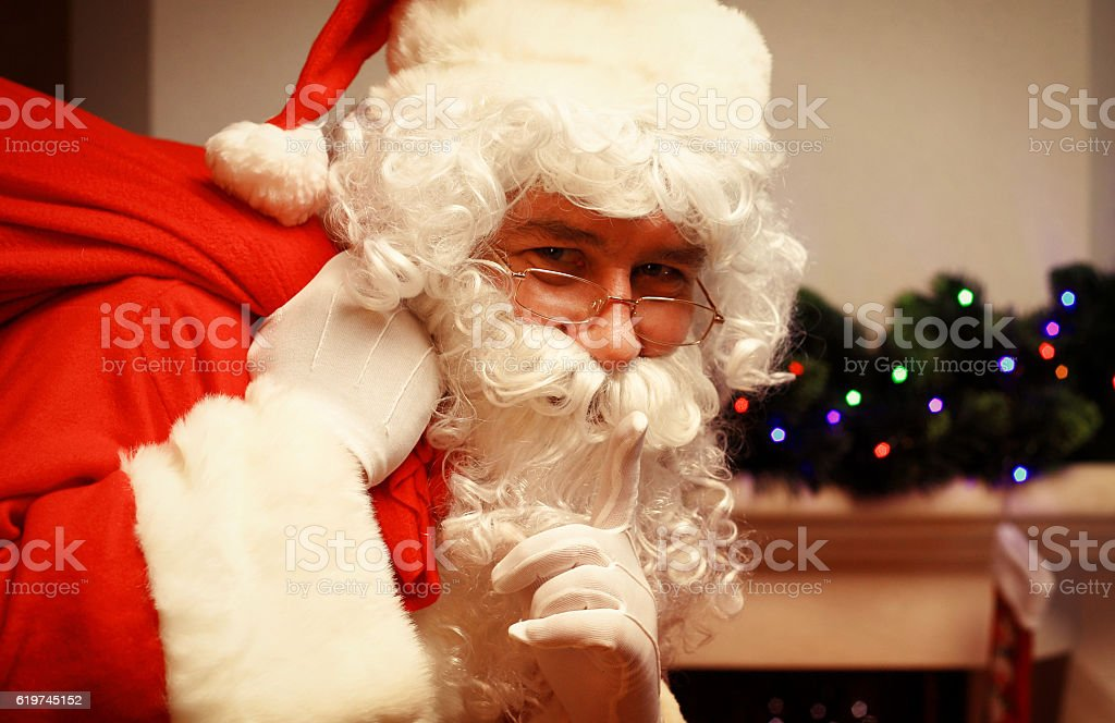 Santa Claus with huge sack keeping forefinger by his mouth stock photo