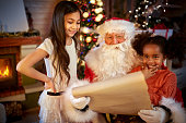 Santa Claus with little girls reading wish list
