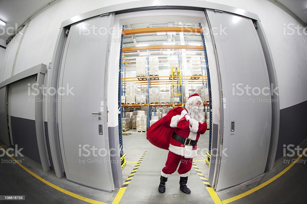 Santa Claus with red sack leaving storehouse full of presents royalty-free stock photo