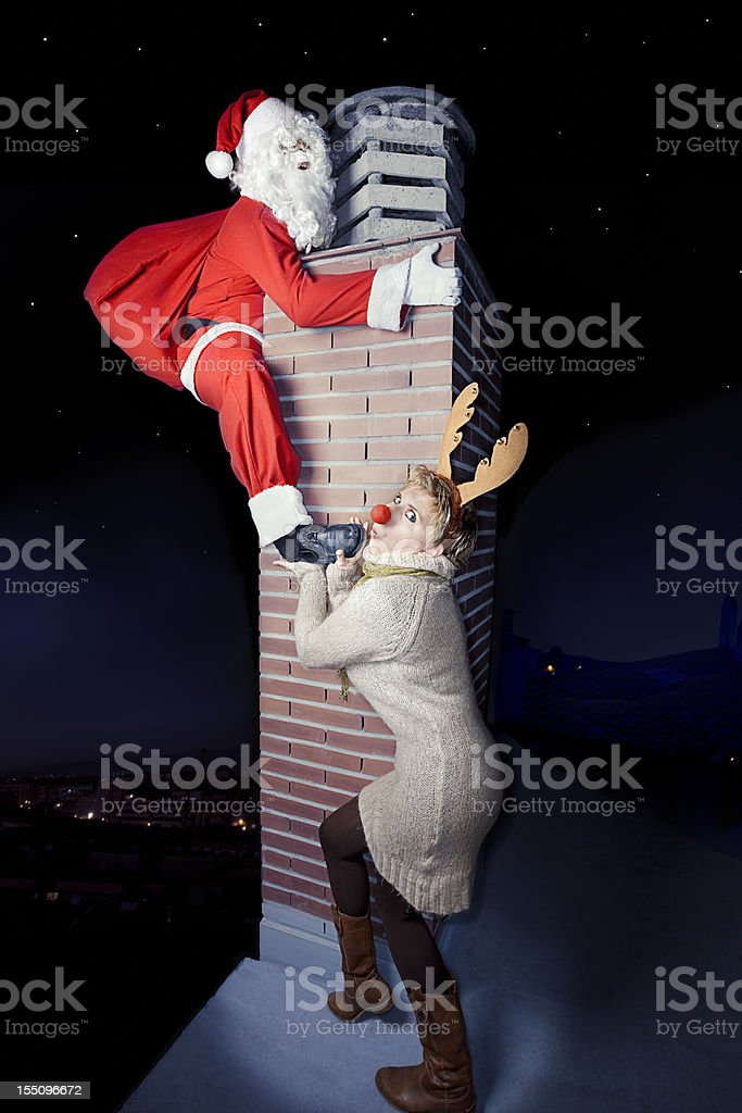 Santa claus with Rudoph in a chimney royalty-free stock photo