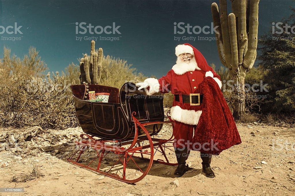 Santa Claus with sleigh in desert stock photo