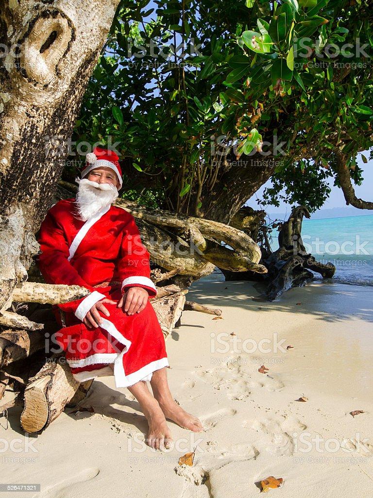 Santa Cloaus  resting on beach stock photo
