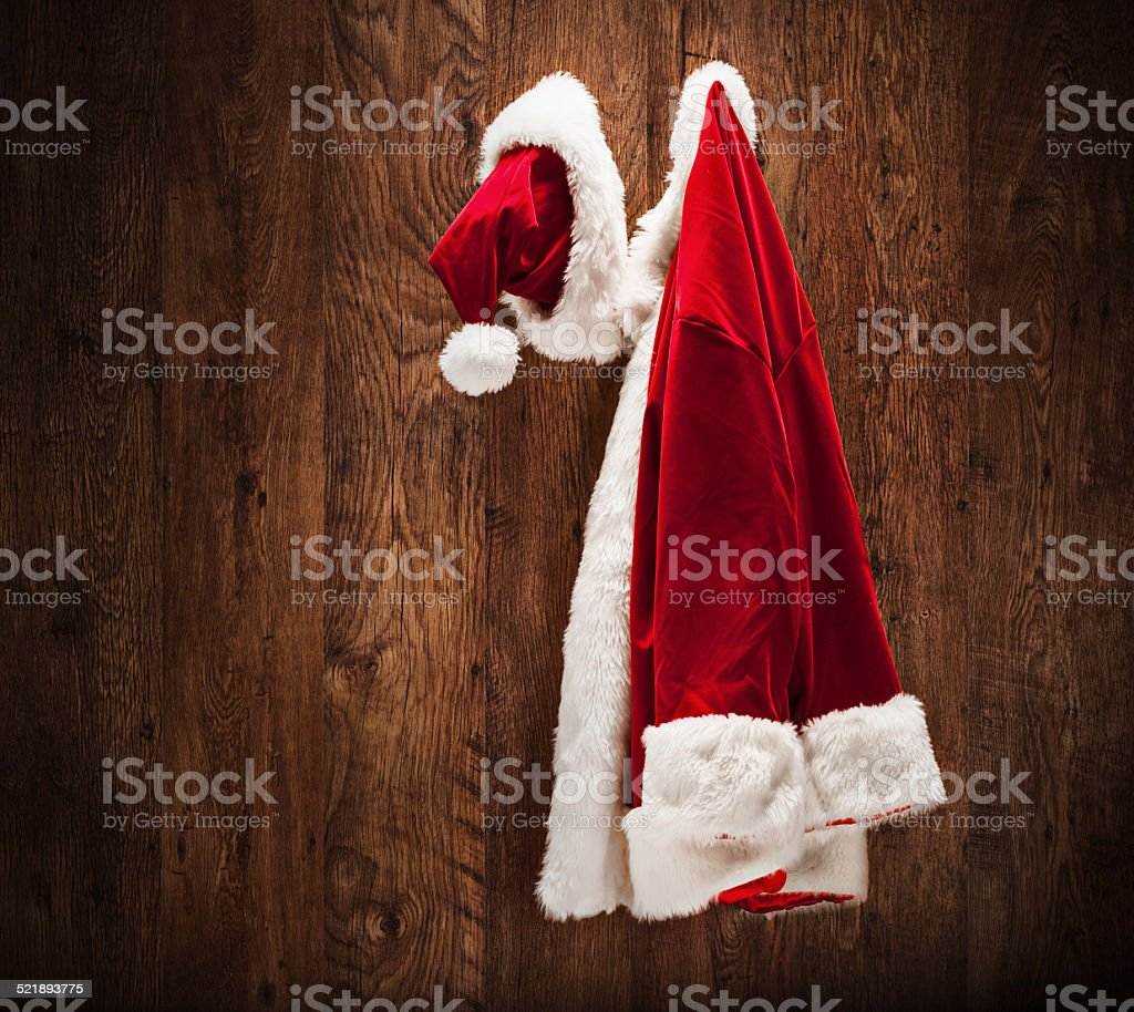 Santa costume hanging on a wooden wall stock photo