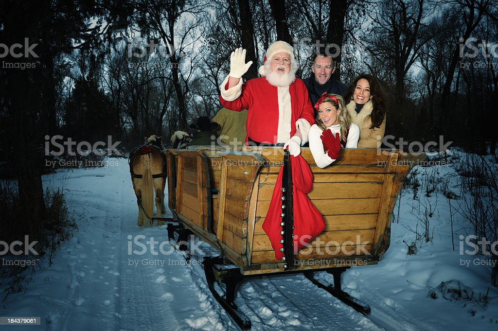 Santa, Elf, and Parents Riding On Sleigh In The Country stock photo