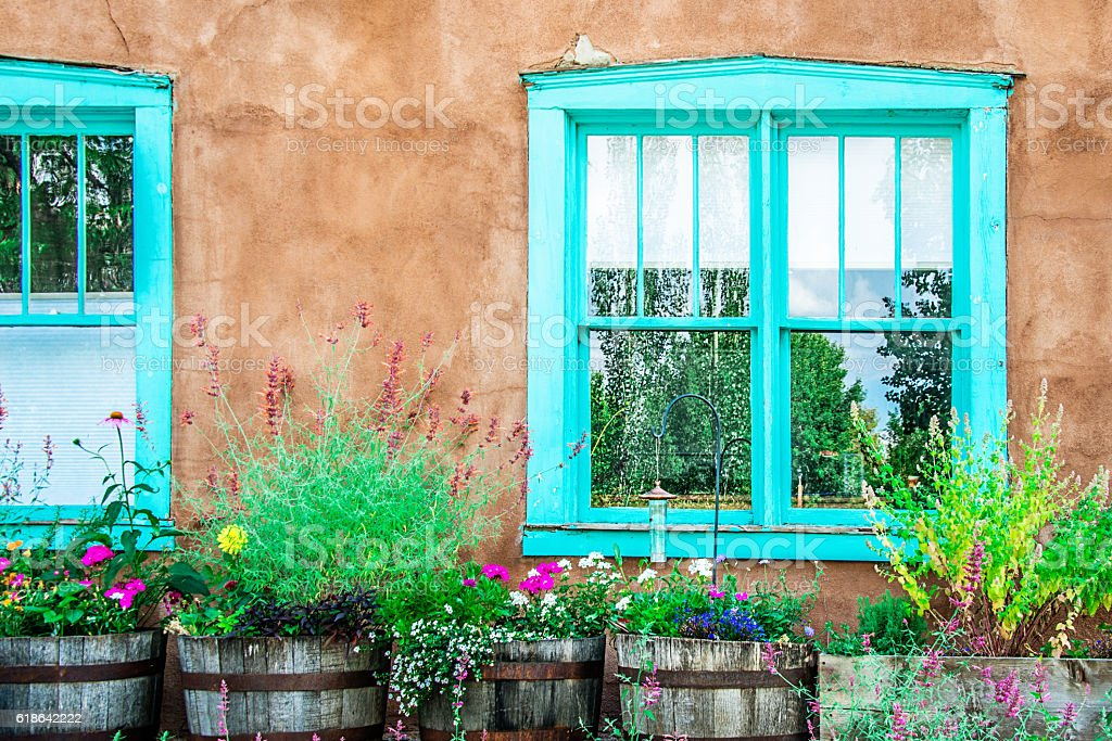 Santa Fe Blue Windows on Stucco Wall with Flowers stock photo