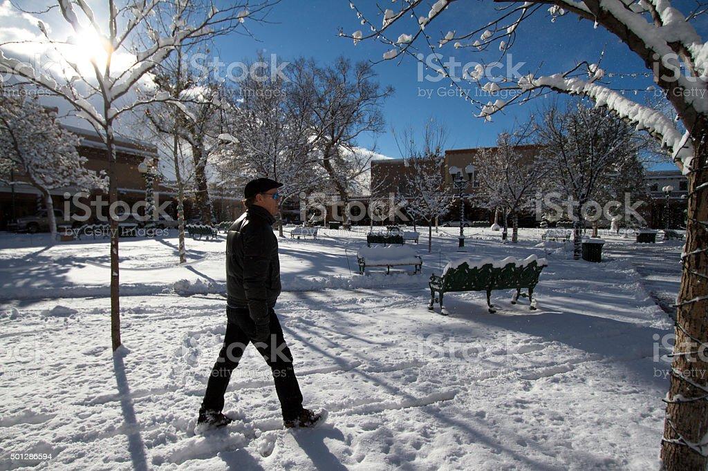 Santa Fe in Snow: Man Walks Across Santa Fe Plaza stock photo