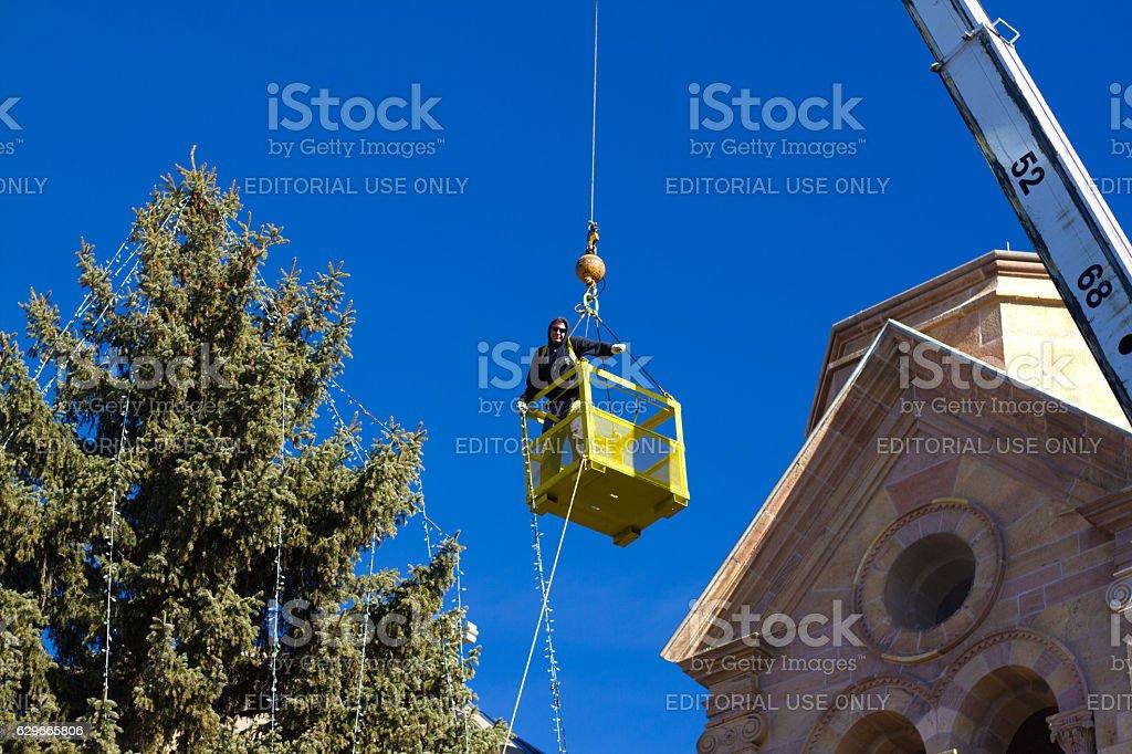 Santa Fe, NM: Stringing Christmas Lights on Cathedral Tree stock photo