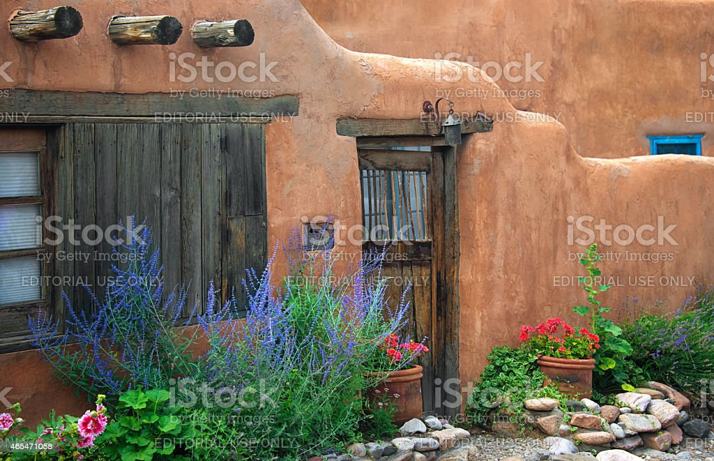 Santa Fe Stucco Wall, Wooden Gate and Flowers stock photo