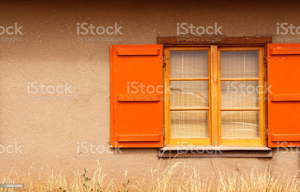 Santa Fe Style: Adobe-Straw Wall, Orange Shutters, Prairie Grass stock photo