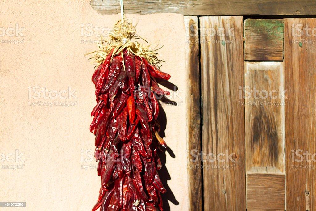Santa Fe Style: Chile Pepper Ristra Hangs Near Wood Door stock photo