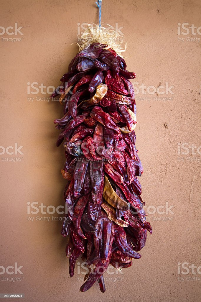 Santa Fe Style: Chile Pepper Ristra Hangs on Adobe Wall stock photo
