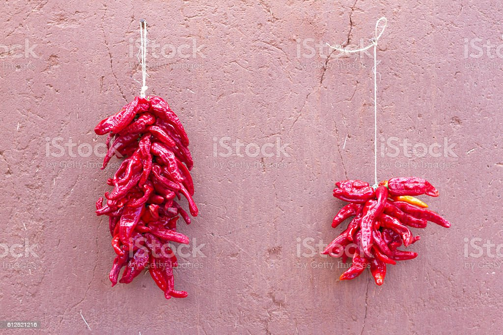 Santa Fe Style: Chile Pepper Ristras on Raw Adobe Wall stock photo