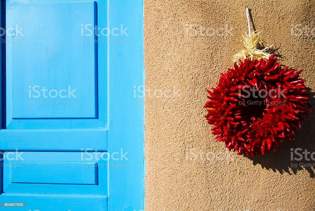 Santa Fe Style: Chili Pepper Wreath, Adobe Wall, Blue Door stock photo