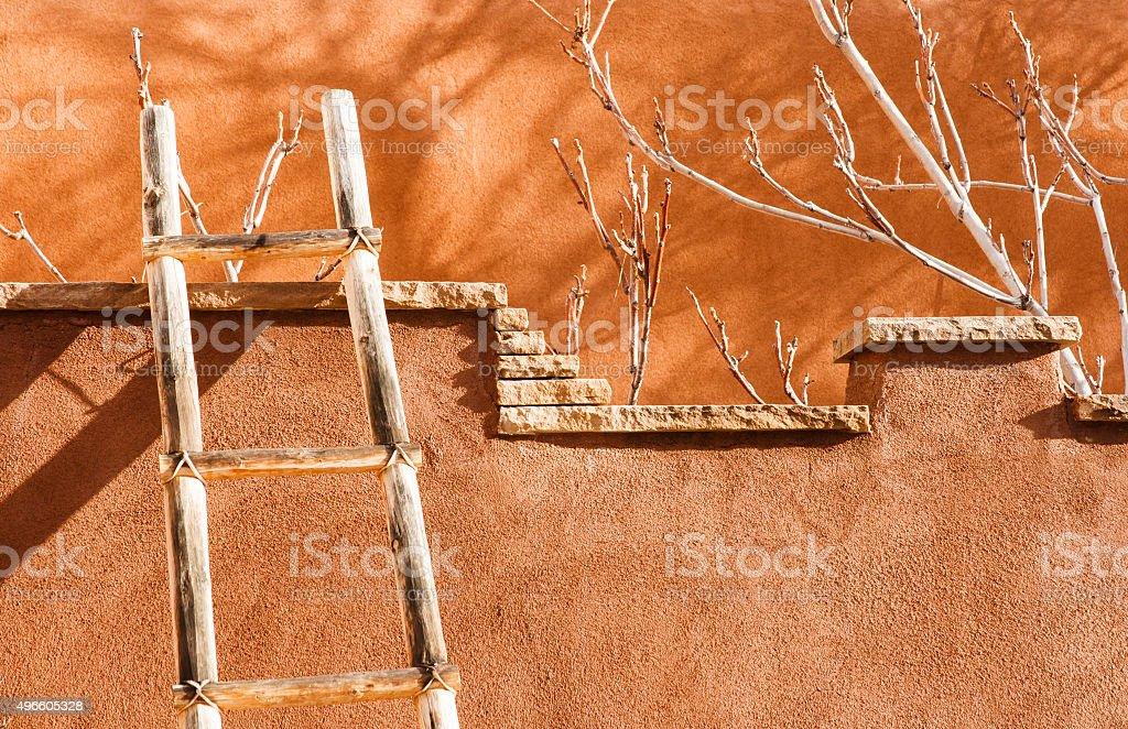 Santa Fe Style: Kiva Ladder Against Brown Adobe Wall, NM stock photo