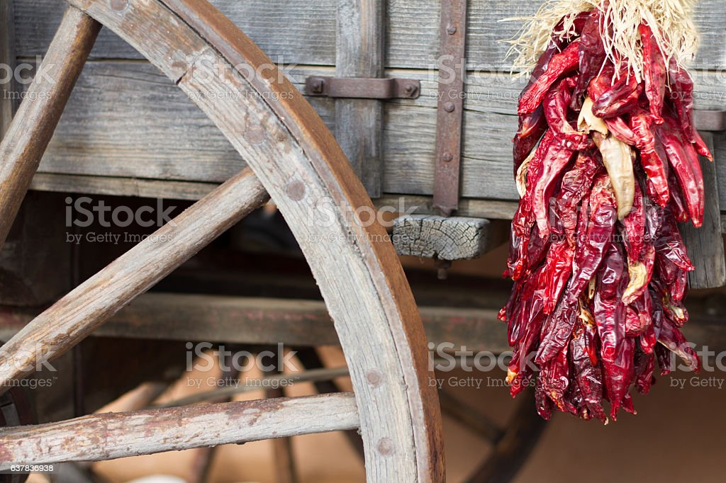 Santa Fe Style: Red Chile Pepper Ristra, Old Wagon Wheel stock photo