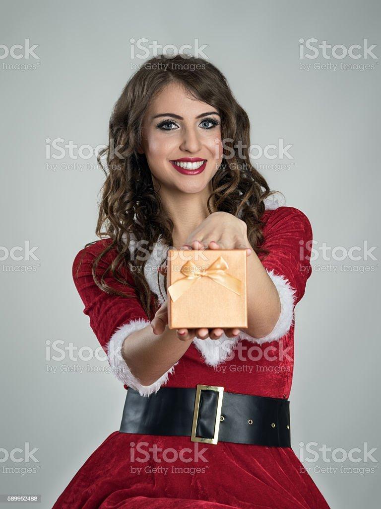 Santa girl giving Christmas gift in golden box to you stock photo