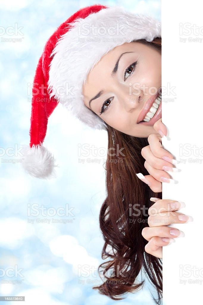 Santa girl peeking behind blank sign board (banner) stock photo