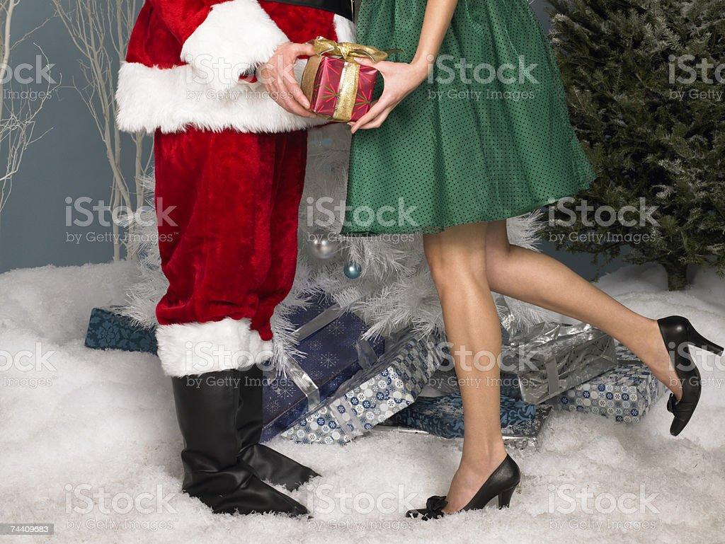 Santa handing a present to a woman royalty-free stock photo