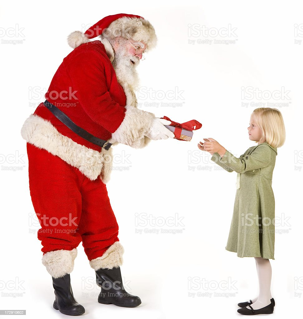 Santa hands gift-wrapped box to adorable little girl royalty-free stock photo