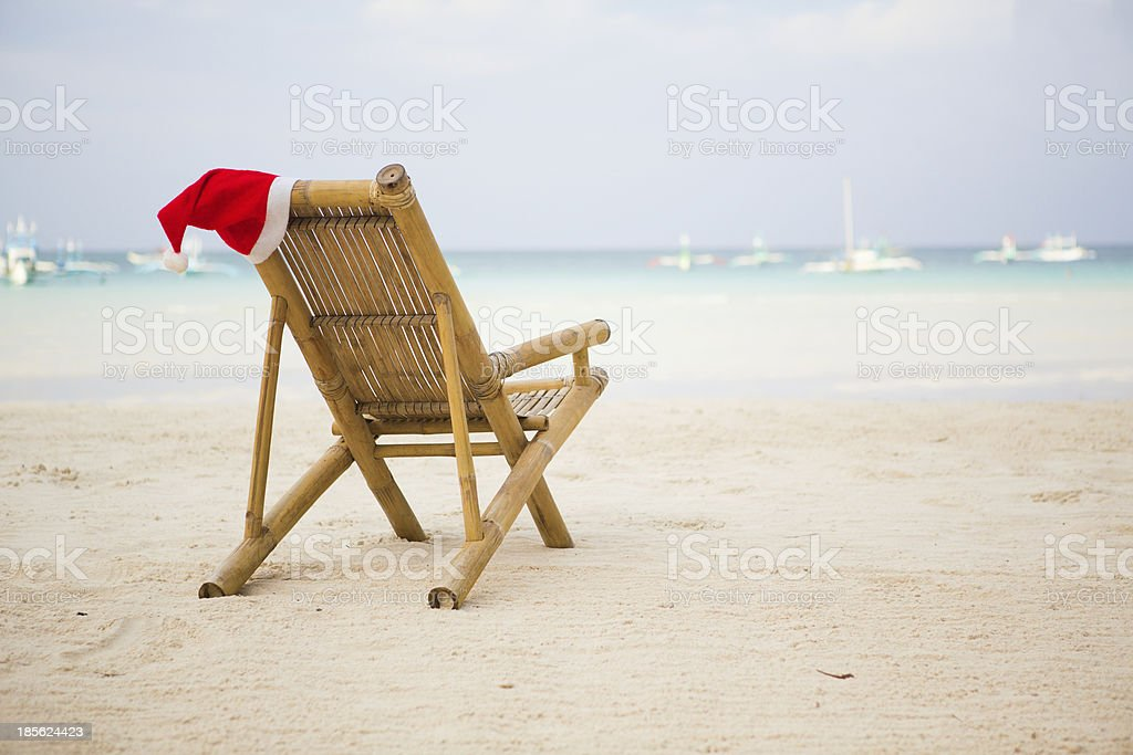 Santa hat on chaise longue at white sand beach royalty-free stock photo
