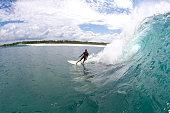 Santa hat surfer girl on a big wave
