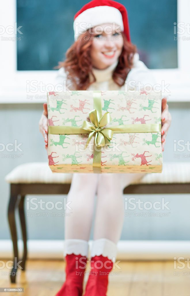 Santa Helper Girl Offers Big Present Box At Front stock photo