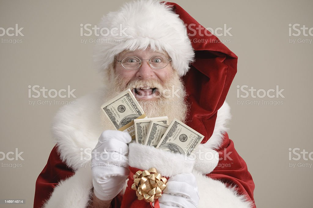 Santa holding a stocking filled with money royalty-free stock photo