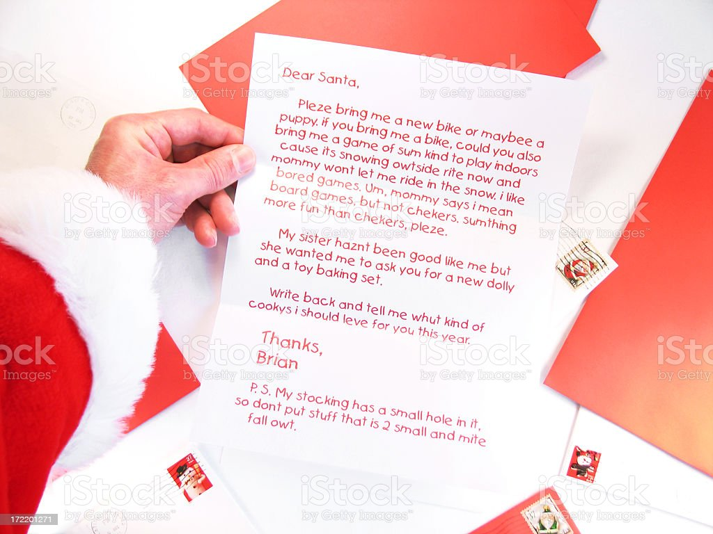 Santa Holds and Reads a Christmas Letter from a Child stock photo
