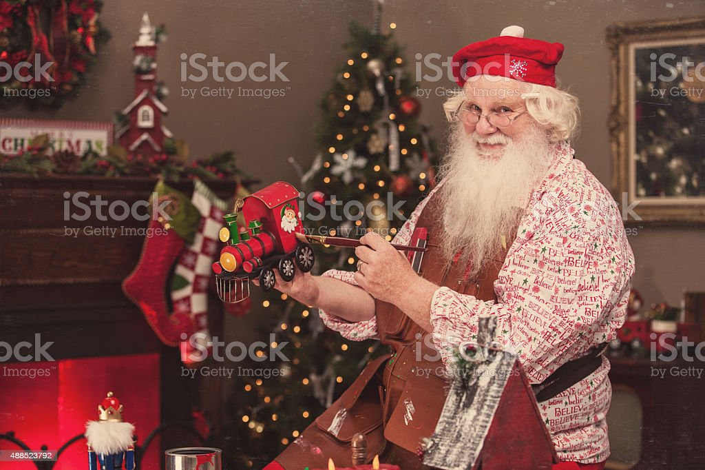 Santa in Workshop Painting Toy Train stock photo