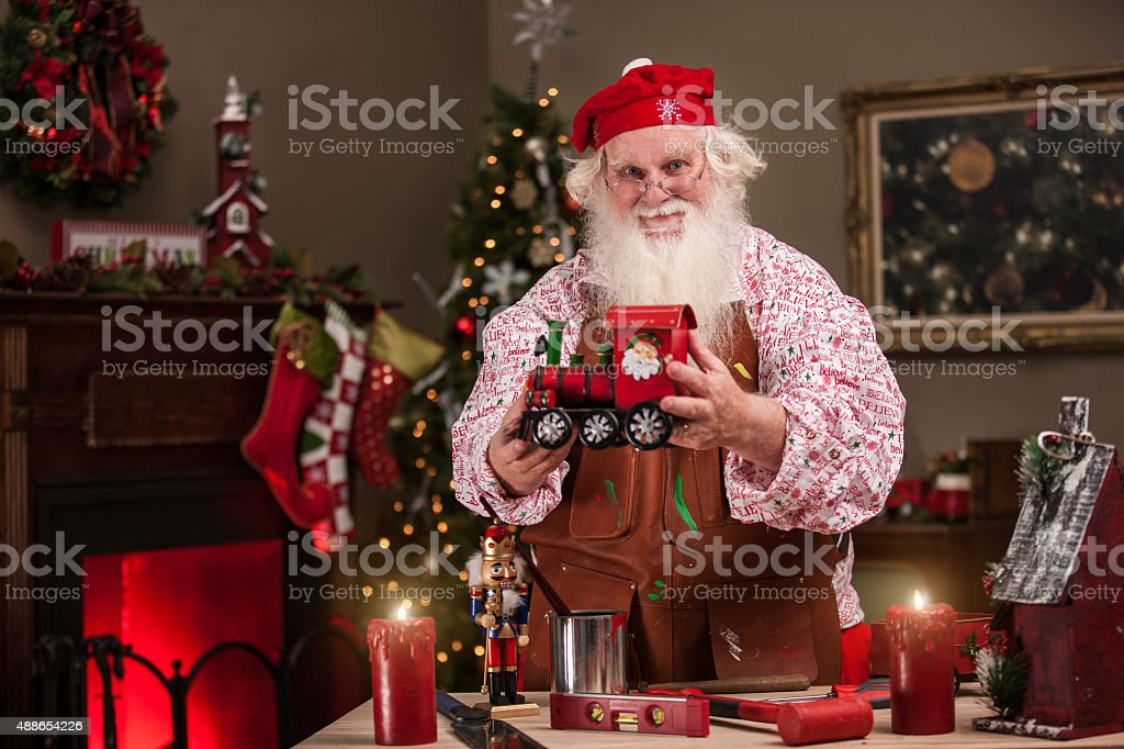 Santa in Workshop Showing a Toy Train stock photo