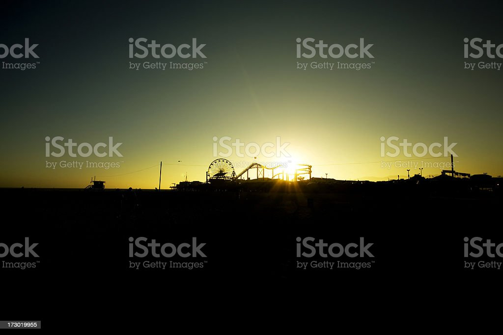 Santa Monica Pier with the Sun Setting Behind it royalty-free stock photo