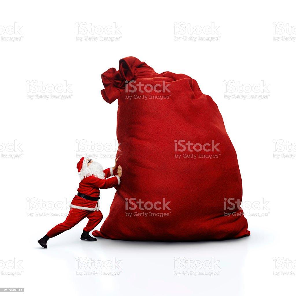 Santa pushing huge sack. Isolated on white. stock photo