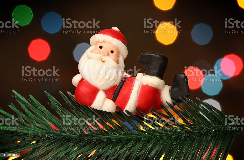 Santa resting over a christmas branch tree royalty-free stock photo