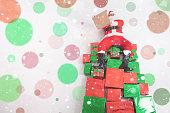 Santa sitting at big gift boxes and reading wish list